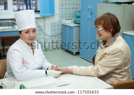 Nurse taking blood sample  from patient in clinic - stock photo