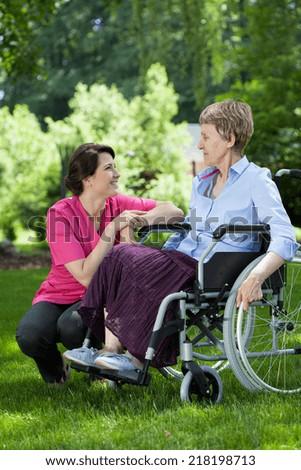 Nurse taking care of elderly woman on wheelchair - stock photo