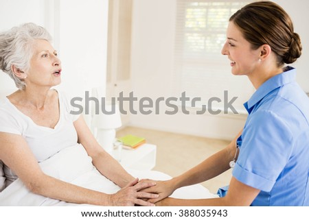 Nurse taking care of suffering senior patient at home - stock photo