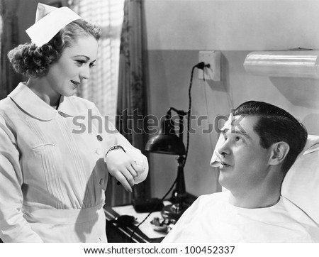 Nurse taking patients temperature - stock photo