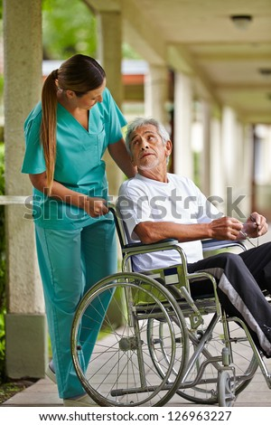 Nurse talking to elderly man in wheelchair in a nursing home - stock photo