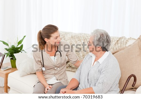 Nurse talking with her patient at home - stock photo
