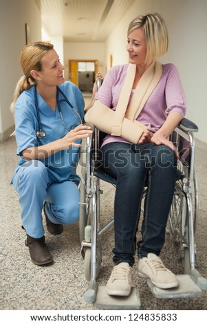 Nurse talking with patient in wheelchair with arm in sling in hospital hallway - stock photo