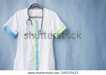 Nurse uniform with stethoscope on hanger - stock photo