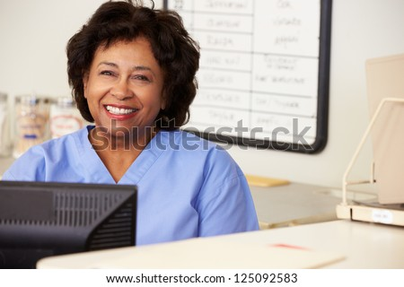 Nurse Using Computer At Nurses Station - stock photo