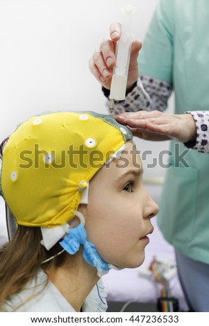 nurse using syringe introduces special gel for electrodes located in cap of electroencephalogram, girl looking to side, focus on syringe - stock photo