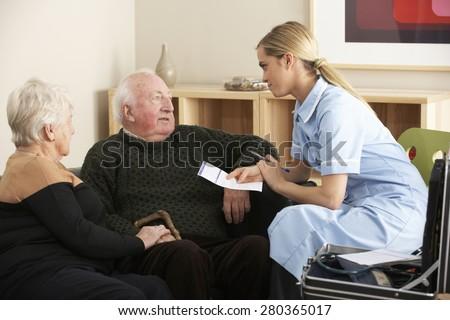 Nurse visiting senior couple at home - stock photo