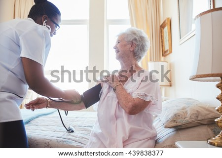 Nurse visiting senior female patient at home and taking blood pressure. Old woman sitting on bed. - stock photo