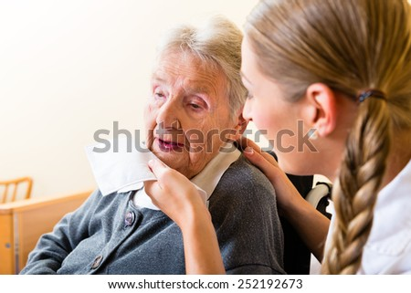 Nurse wiping mouth of elderly senior woman in nursing home - stock photo