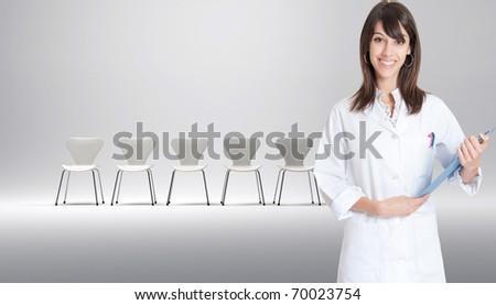 Nurse with a row of white chairs at the background - stock photo