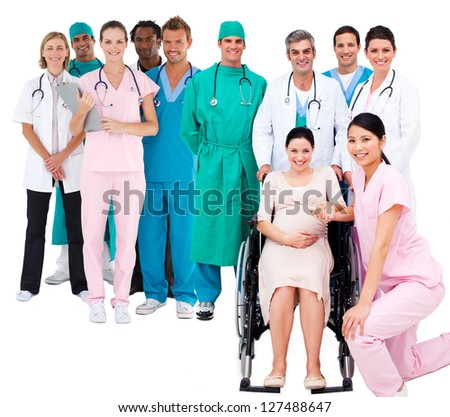 Nurse with pregnant woman in wheelchair with medical staff standing behind on white background - stock photo
