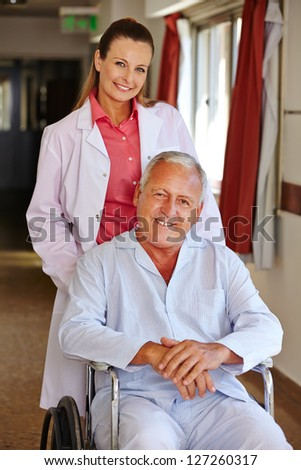 Nurse with senior man in wheelchair in a hospital - stock photo