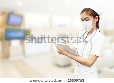 nurse with stethoscope writing medical report in hospital background - stock photo