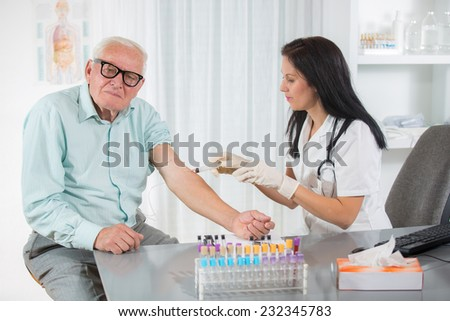 Nurse with syringe is taking blood for test at the doctor office - stock photo