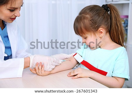 Nurse with syringe is taking blood for test in hospital - stock photo