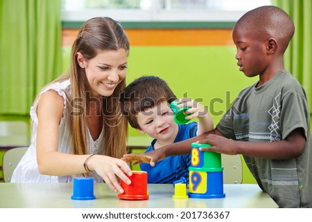 Nursery teacher building tower with children in a kindergarten - stock photo