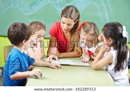 Nursery teacher reading book aloud to children in a kindergarten group - stock photo