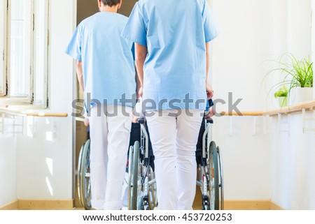 Nurses pushing seniors in wheelchair thru nursing home - stock photo
