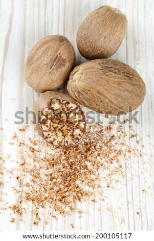 nutmeg on wooden surface - stock photo