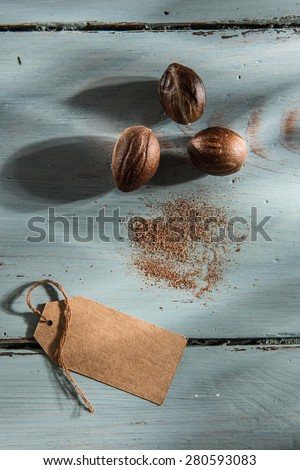 nutmeg with a blank label, on a wooden background - stock photo