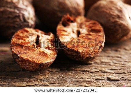 Nutmegs on wooden background - stock photo