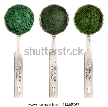 Nutrient-rich organic blue green algae, chlorella and spirulina powder - isolated measuring metal tablespoons, top view - stock photo
