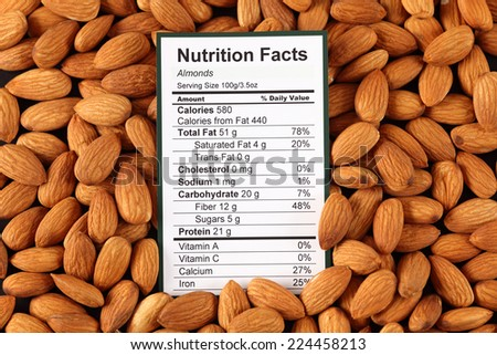 Nutrition facts of almonds with almonds background  - stock photo