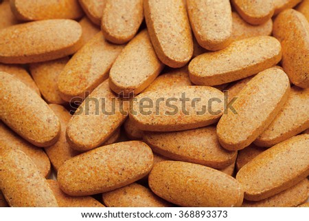 nutrition supplements, macro view of orange vitamin pills - stock photo