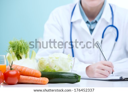 Nutritionist Doctor writing a diet plan - stock photo