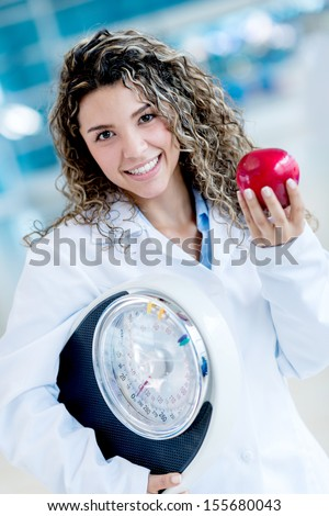 Nutritionist holding a weight scale and an apple - healthy lifestyle  - stock photo