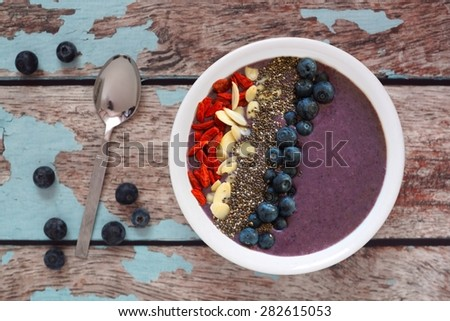 Nutritious blueberry smoothie bowl with goji berries, almonds and chia seeds on a rustic old wood background - stock photo