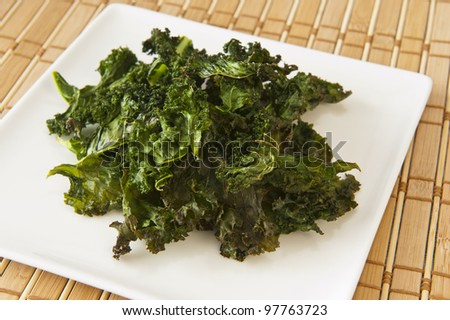 Nutritious snack of roasted kale chips on a white plate - stock photo