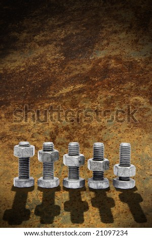 nuts and bolts with shadow on a rusty background - stock photo