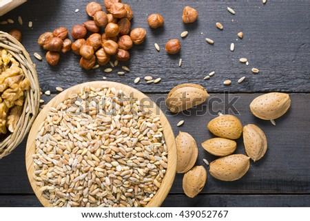 nuts and cereal seeds on black wood table background - stock photo