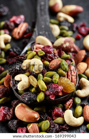 Nuts and dried fruits mix on wooden spoon - stock photo