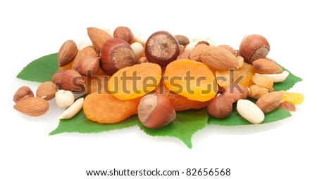 nuts and dried fruits on green leaves isolated on white background - stock photo