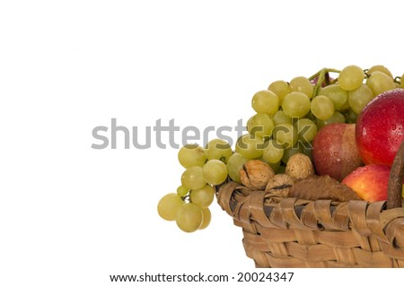 Nuts, apples and grapes in a wicker basket on white background - stock photo
