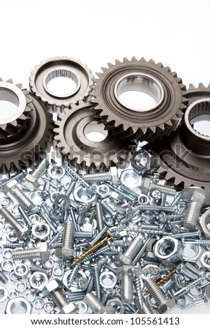 Nuts, bolts and cogs on plain background - stock photo