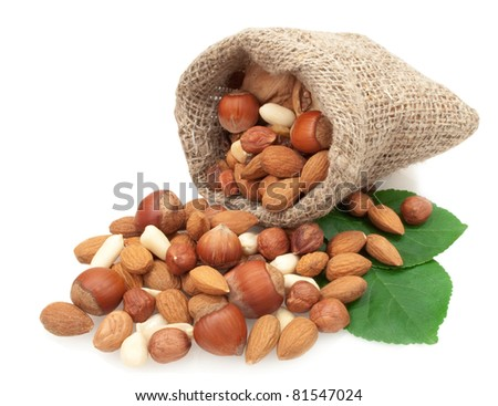 nuts in a linen basket on green leaves isolated on white background - stock photo