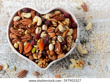 Nuts on heart plate. Healthy eating. Top view - stock photo