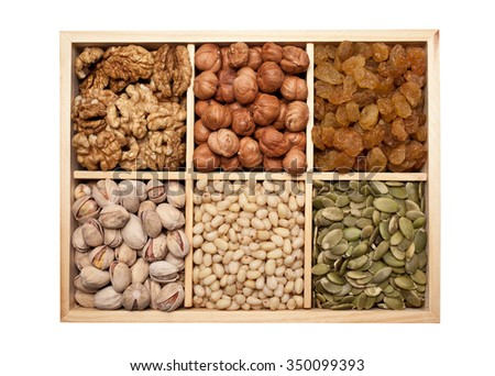 Nuts, seeds and raisins in a wooden box - stock photo