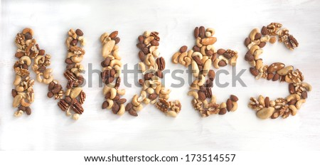 Nuts word from different nuts. Mixed nuts - hazelnuts, walnuts,  - stock photo