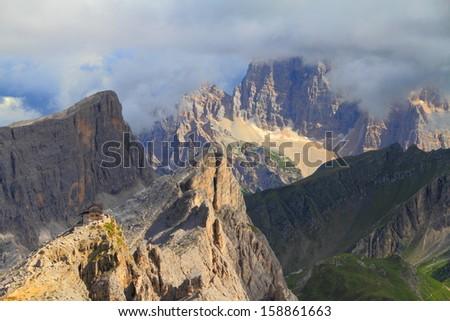 Nuvolau refuge and mountain peaks under gloomy sky, Dolomite Alps, Italy - stock photo