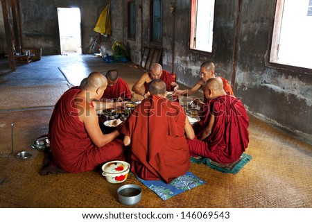 NYAUNGSHWE, MYANMAR - FEBRUARY 2: Buddhist monks have the scanty dinner in Shwe Yan Pyay on February 2, 2011 in Nyaungswe, Shan, Myanmar. The Buddhism is important part of social life in the Myanmar. - stock photo