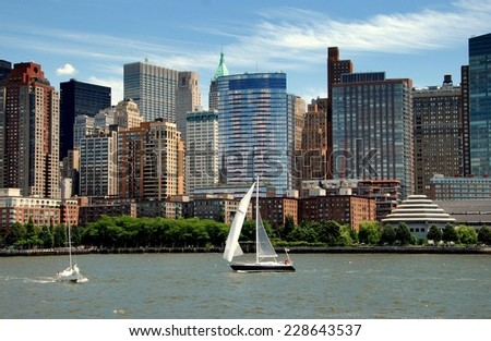 NYC - July 19, 2009: Sailboat passes the skyline of lower Manhattan island at Battery Park City with the Jewish Holocaust Museum with tiered roof at bottom right - stock photo