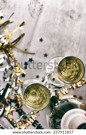 NYE Background: Focus On Glasses Of Champagne Amidst Confetti And Favors - stock photo