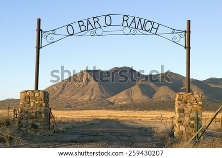 O'Bar'o Ranch gate and mountains at sunset in central New Mexico, Route 48 near Smokey Bear Historical Park - stock photo
