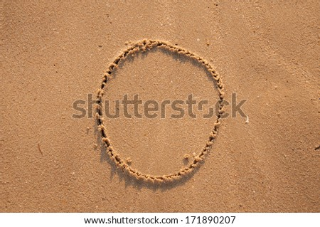 O text written in the sandy on the beach - stock photo