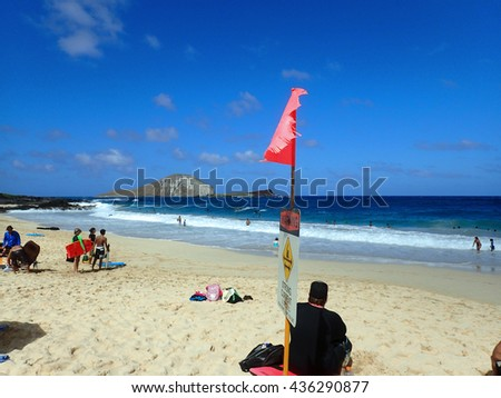 OAHU - FEBRUARY 14: People play at the beach with strong current sign on beach and view of islands Rabbit and Rock on a clear day at Makapuu Beach Park, Oahu, Hawaii.   February 14, 2016. - stock photo