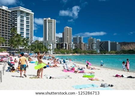 OAHU, HI - SEPTEMBER 27, 2011 - Tourist sunbathing and surfing on Waikiki beach September 27, 2011 in Oahu.  Waikiki beach is beachfront neighborhood of Honolulu, best known for white sand and surfing - stock photo